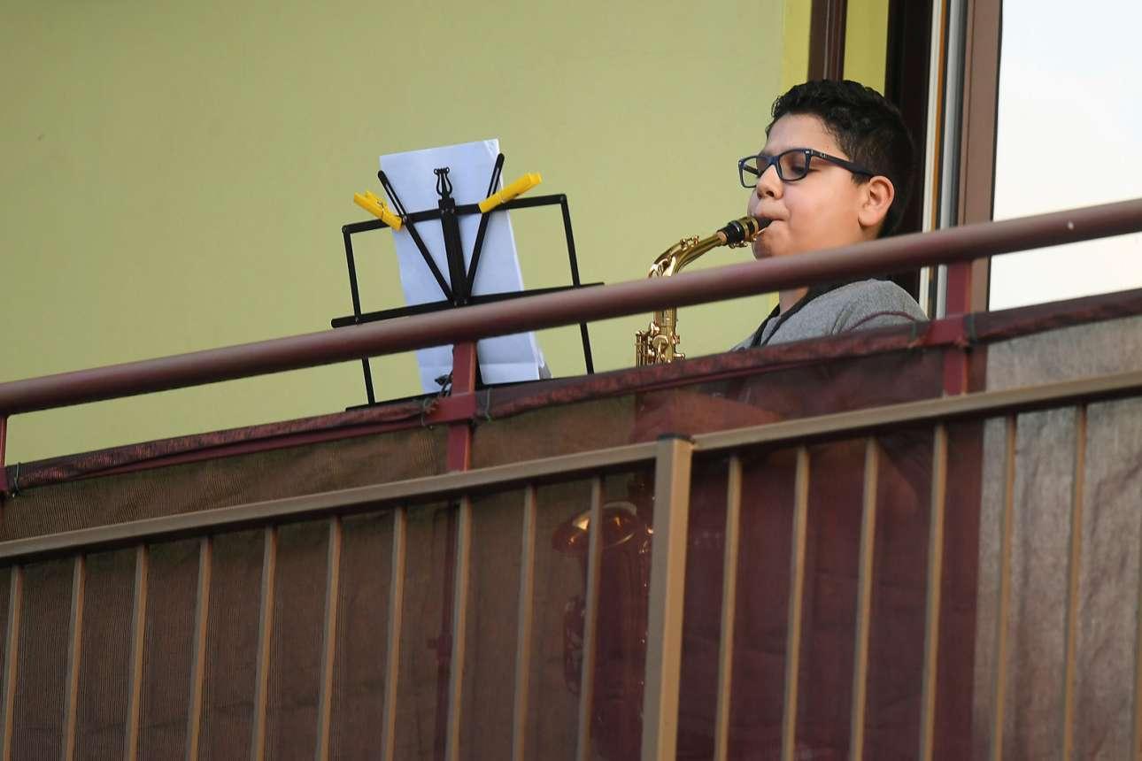 Ενα νεαρό αγόρι παίζει σαξόφωνο στο μπαλκόνι του στην Ρώμη για να εμψυχώσει τους συμπατριώτες του