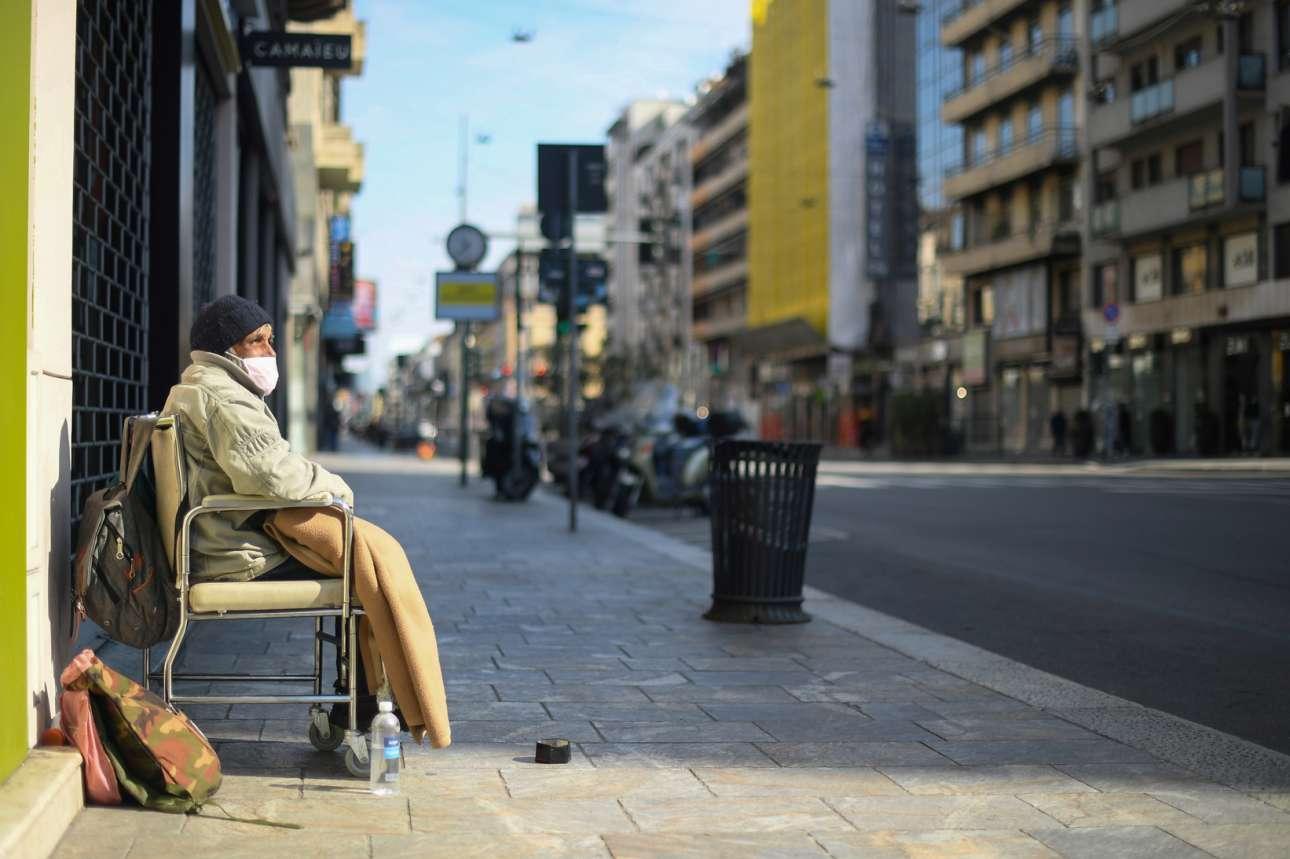 Ενας άστεγος με προστατευτική μάσκα κοιτάζει τον άλλοτε πολυσύχναστο δρόμο Corso Buenos Aires στο Μιλάνο