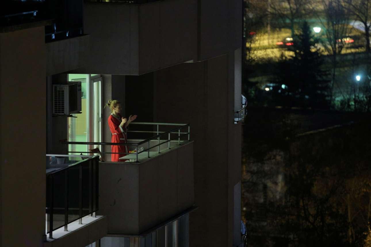 Μία γυναίκα στη Σόφια βγαίνει στο μπαλκόνι της να χειροκροτήσει το ιατρικό προσωπικό της Βουλγαρίας