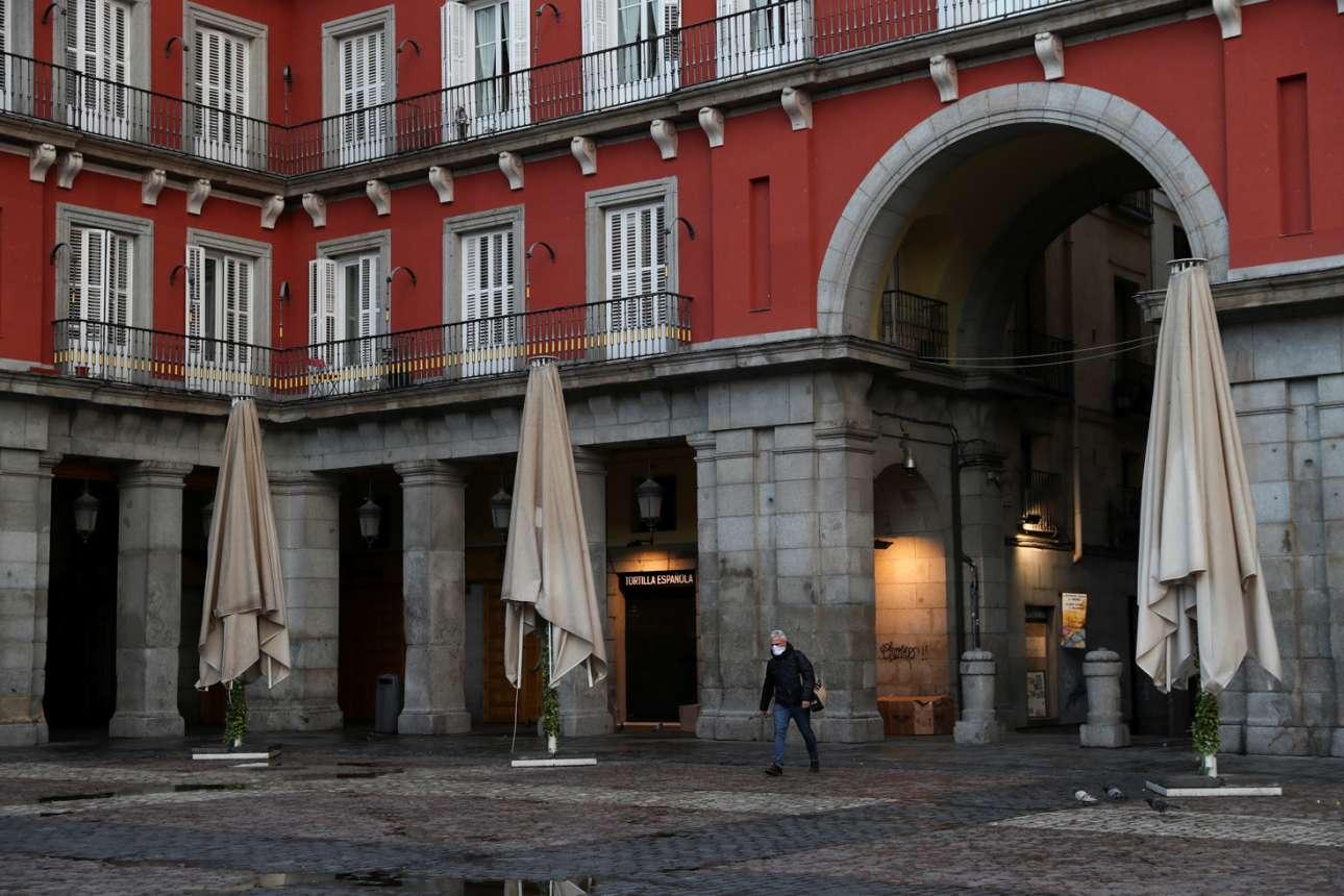Ενας άνδρας με μάσκα διασχίζει τη φημισμένη Πλάθα Μαγιόρ, την κεντρική πλατεία της Μαδρίτης. Ο κορονοϊός καλπάζει στην Ισπανία και όλα τα καταστήματα θα παραμείνουν κλειστά για 15 ημέρες