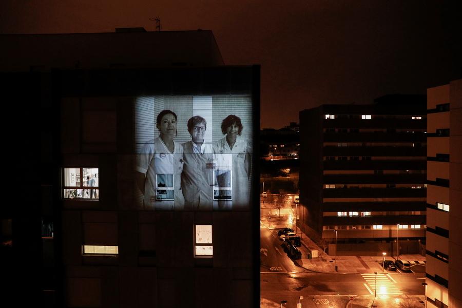 Μια εικόνα με υγειονομικό προσωπικό προβάλλεται πάνω σε πολυκατοικία στη Παμπλόνα την Ισπανίας, την προγραμματισμένη ώρα που κάτοικοι βγαίνουν στα μπαλκόνια τους για να τους χειροκροτήσουν για τον αγώνα τους κατά του κορονοϊού