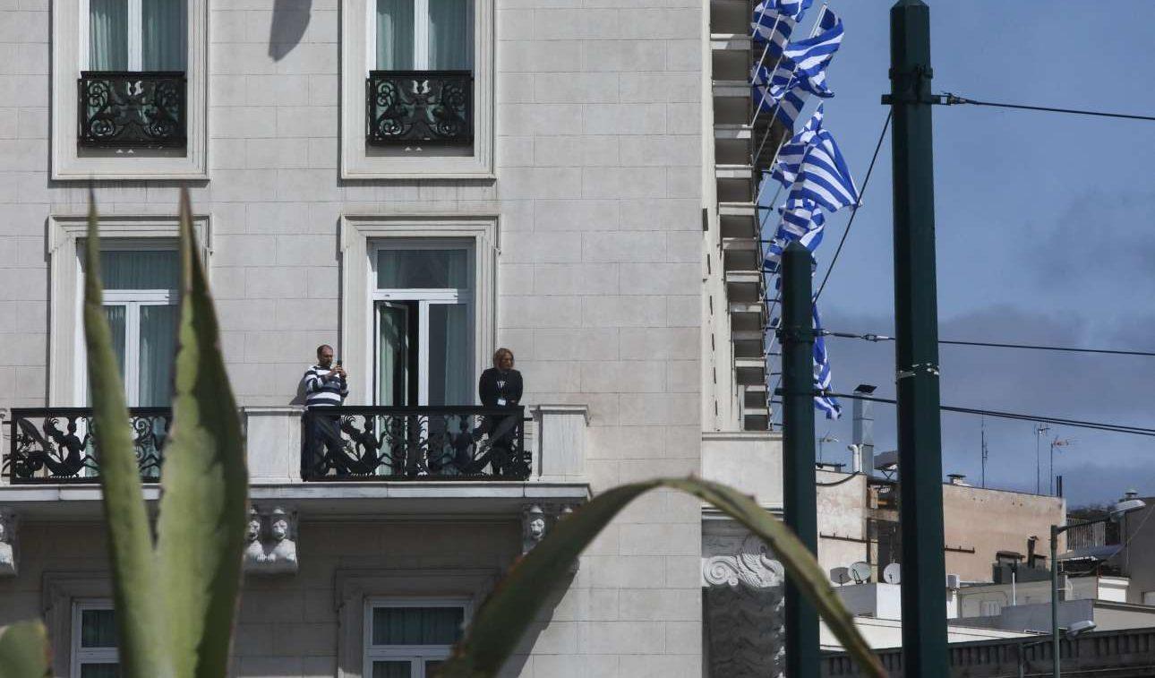Κάποιοι παρακολουθούν το ιδιότυπο τελετουργικό από το μπαλκόνι του ξενοδοχείου «Μεγάλη Βρετανία», που τυπικά είναι κλειστό