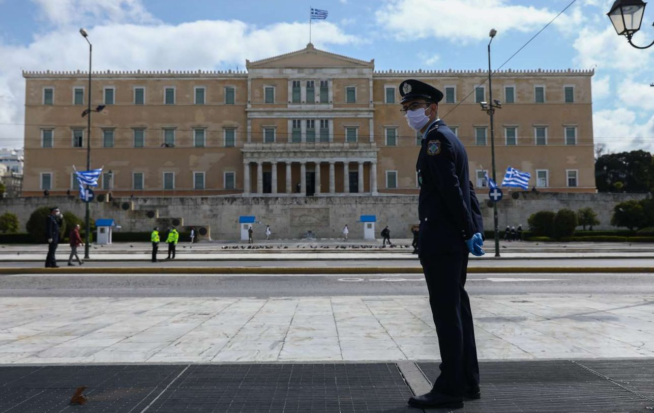 Αστυνομικός με χειρουργική μάσκα επιθεωρεί τον χώρο στην πλατεία Συντάγματος