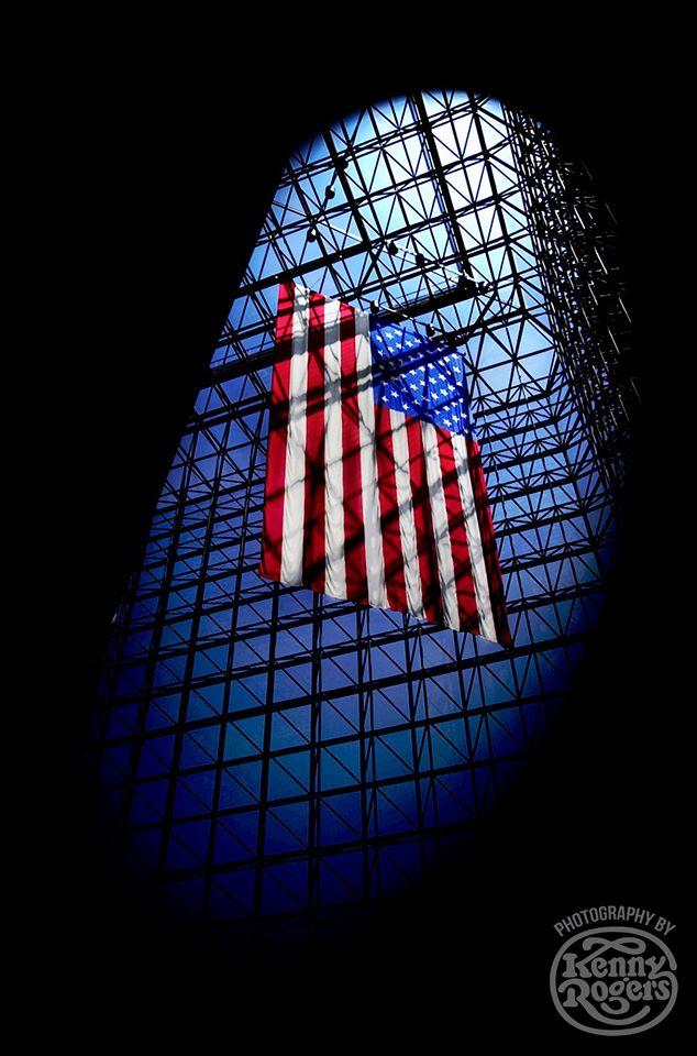 Η αμερικανική σημαία ανάμεσα σε σιδεριές. Ο Ρότζερς συχνά «παίζει» με τις σκιές στις φωτογραφίες του, αποκαλύπτοντας μια πιο σκοτεινή και απειλητική πλευρά της Αμερικής
