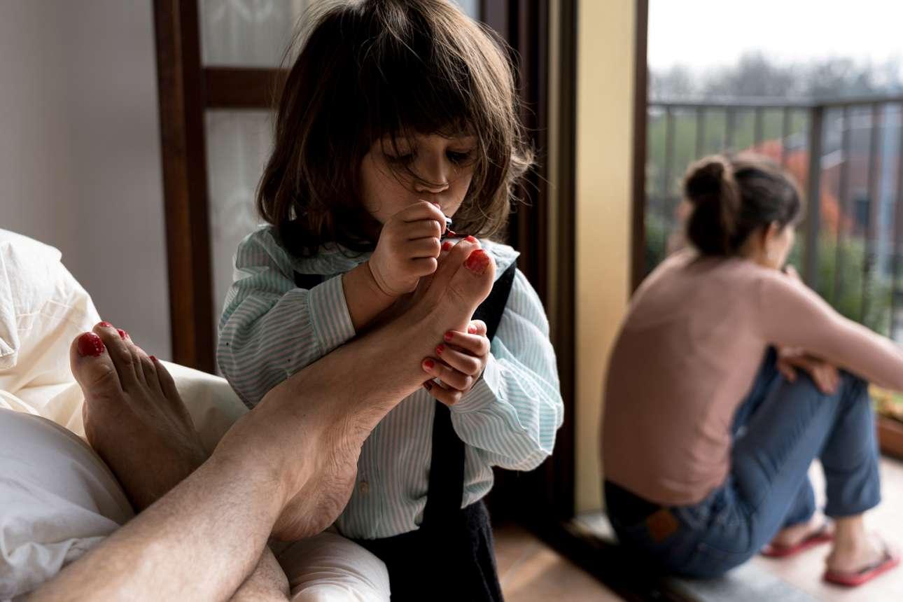 O Μάρτζιο Τονιόλο αιχμαλωτίζει τη ζωή της οικογένειας του από τότε που ξεκίνησε η καραντίνα τον Φεβρουάριο στο Σαν Φιοράνο, μία από τις πρώτες «κόκκινες ζώνες» στην βόρεια Ιταλία. Στην παραπάνω φωτογραφία, ο 35χρονος δάσκαλος απαθανατίζει τη δίχρονη κόρη του Μπιάνκα να του βάφει τα νύχια. Στο φόντο, η σύντροφος του κοιτάζει έξω από το παράθυρο