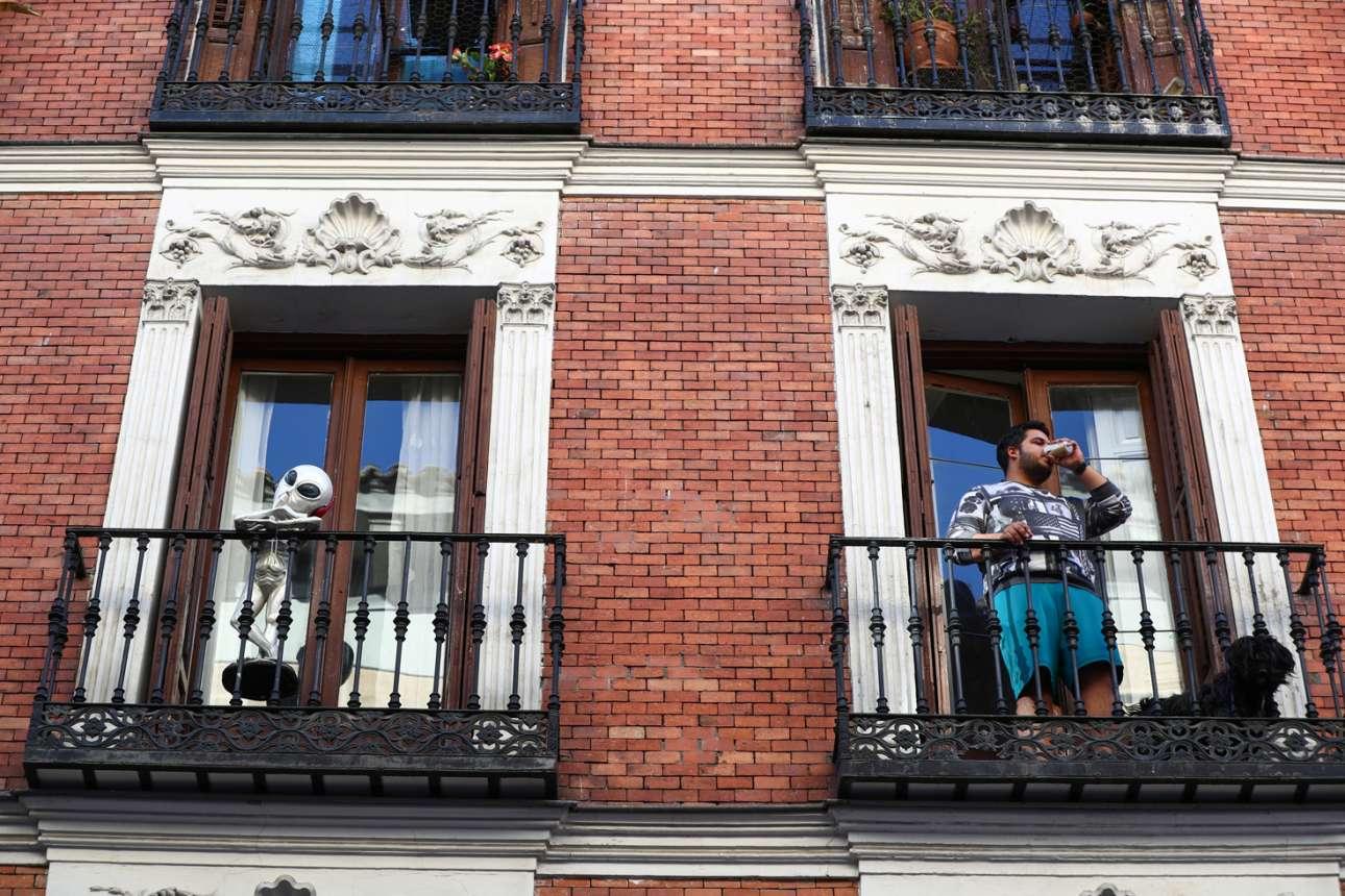 Ενας άνδρας πίνει καφέ στο μπαλκόνι του στη Μαδρίτη, δίπλα σε ένα γλυπτό εξωγήινου...η ζώη μας πλέον δεν έχει τίποτα να «ζηλέψει» από ταινία επιστημονικής φαντασίας