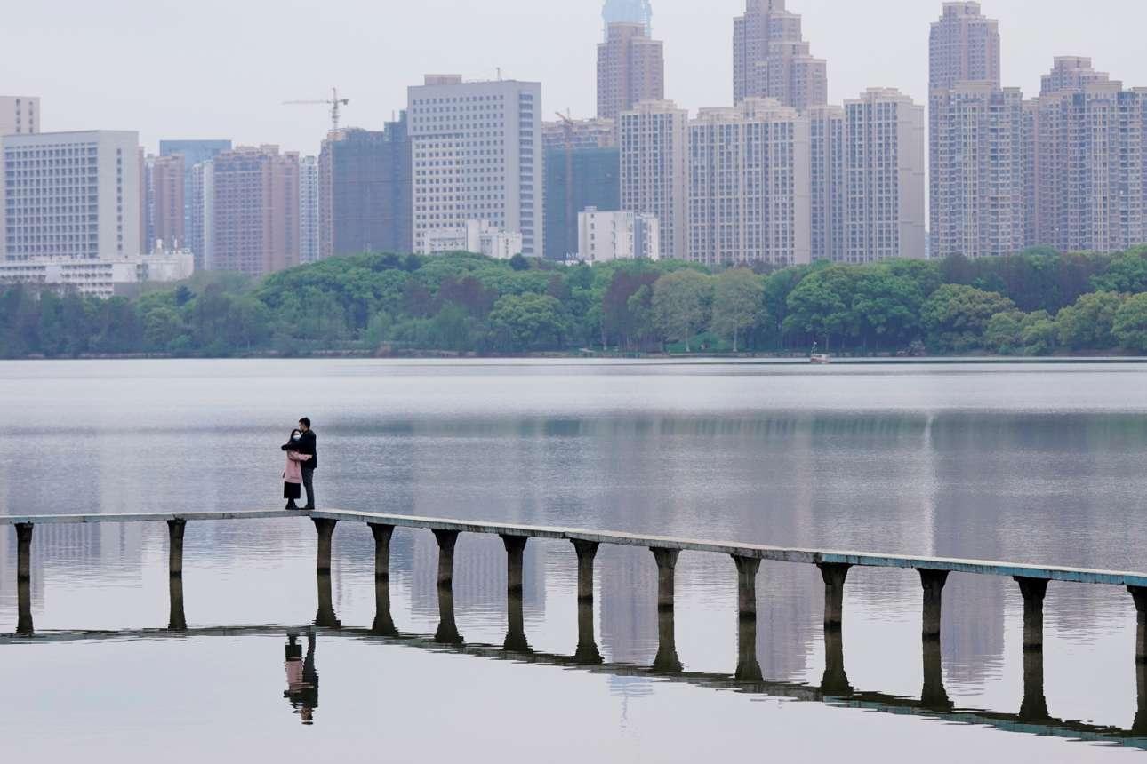Η ζωή επανέρχεται σιγά σιγά στη Γουχάν... ένα ζευγάρι φορώντας μάσκες αγκαλιάζεται στην Ανατολική Λίμνη της κινεζικής πόλης