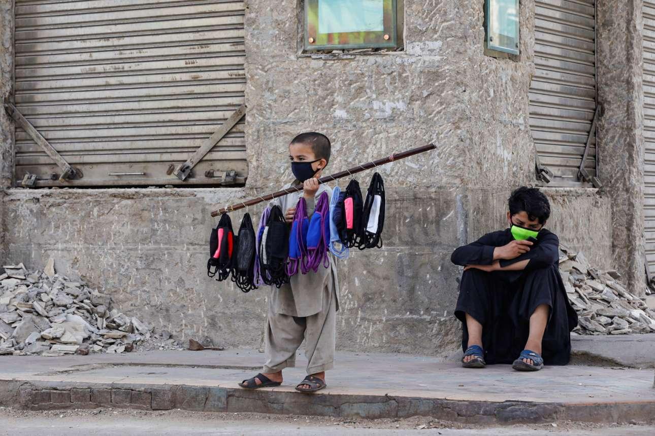 Καράτσι, Πακιστάν. «Η πανδημία στη δουλειά της, και εγώ στη δική μου»: επτάχρονος στο μεροκάματο, πουλάει μάσκες χύμα, κρεμασμένες στο κοντάρι σαν κιλότες του παζαριού. Αμα κουραστεί, θα «τον αλλάξει» ο μεγαλύτερος αδελφός του