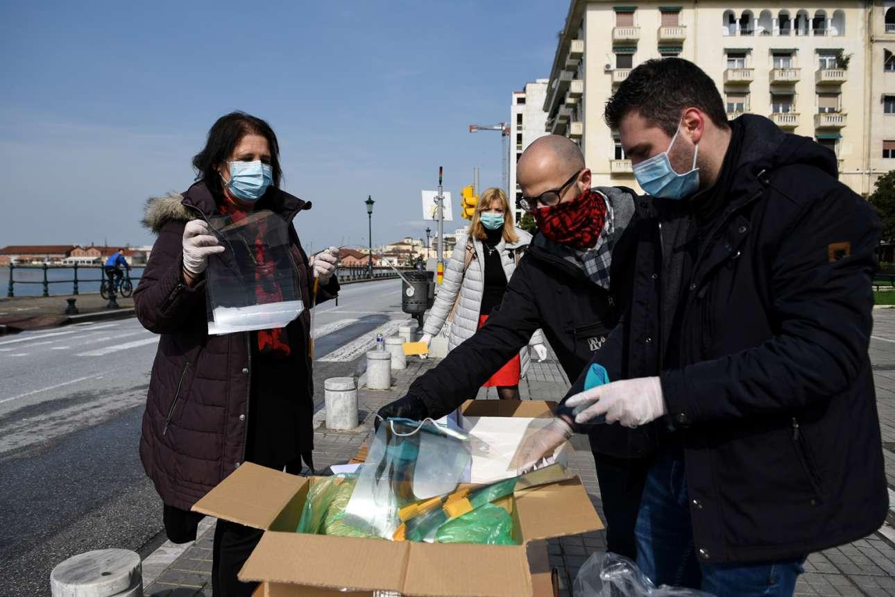 Πλατεία Αριστοτέλους: μέλη του Ιατρικού Συλλόγου Θεσσαλονίκης διανέμουν στους γιατρούς υφασμάτινες μάσκες και ασπίδες προσώπου, οι οποίες δημιουργήθηκαν με 3D εκτυπωτή από την εθελοντική ομάδα «COVID-19 Response Greece»