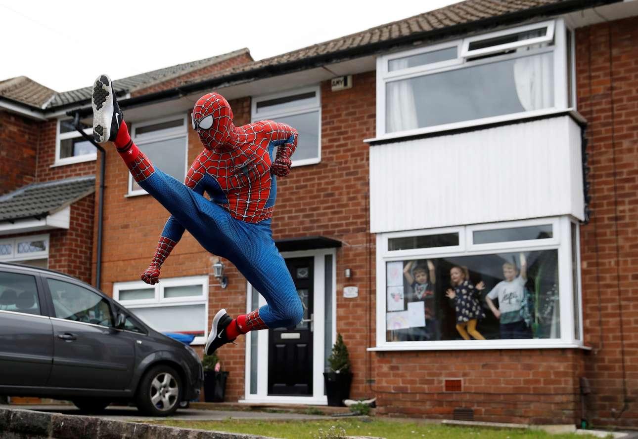 Στόκπορτ, Βρετανία. Ο Σπάιντερμαν αθλείται στον δρόμο και τα πιτσιρίκια, πίσω από το παράθυρο του σπιτιού τους, τον βλέπουν και παλαβώνουν
