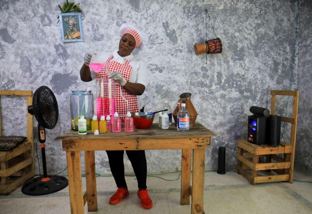 Η 41ετών Ρόουζ Εντίτ Λουκού γεμίζει μπουκάλια με σπιτικό σαπούνι φτιαγμένο στο εστιατόριο της στο Αμπιτζάν, τη μεγαλύτερη πόλη της Ακτής Ελεφαντοστού