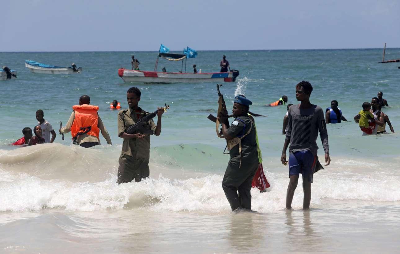Μογκαντίσου, Σομαλία. Αστυνομικοί (με βαρύ οπλισμό) διώχνουν τον κόσμο μακριά από τα νερά του Ινδικού Ωκεανού. Πρόκειται για μέτρο προστασίας τους από τον κορονοϊό