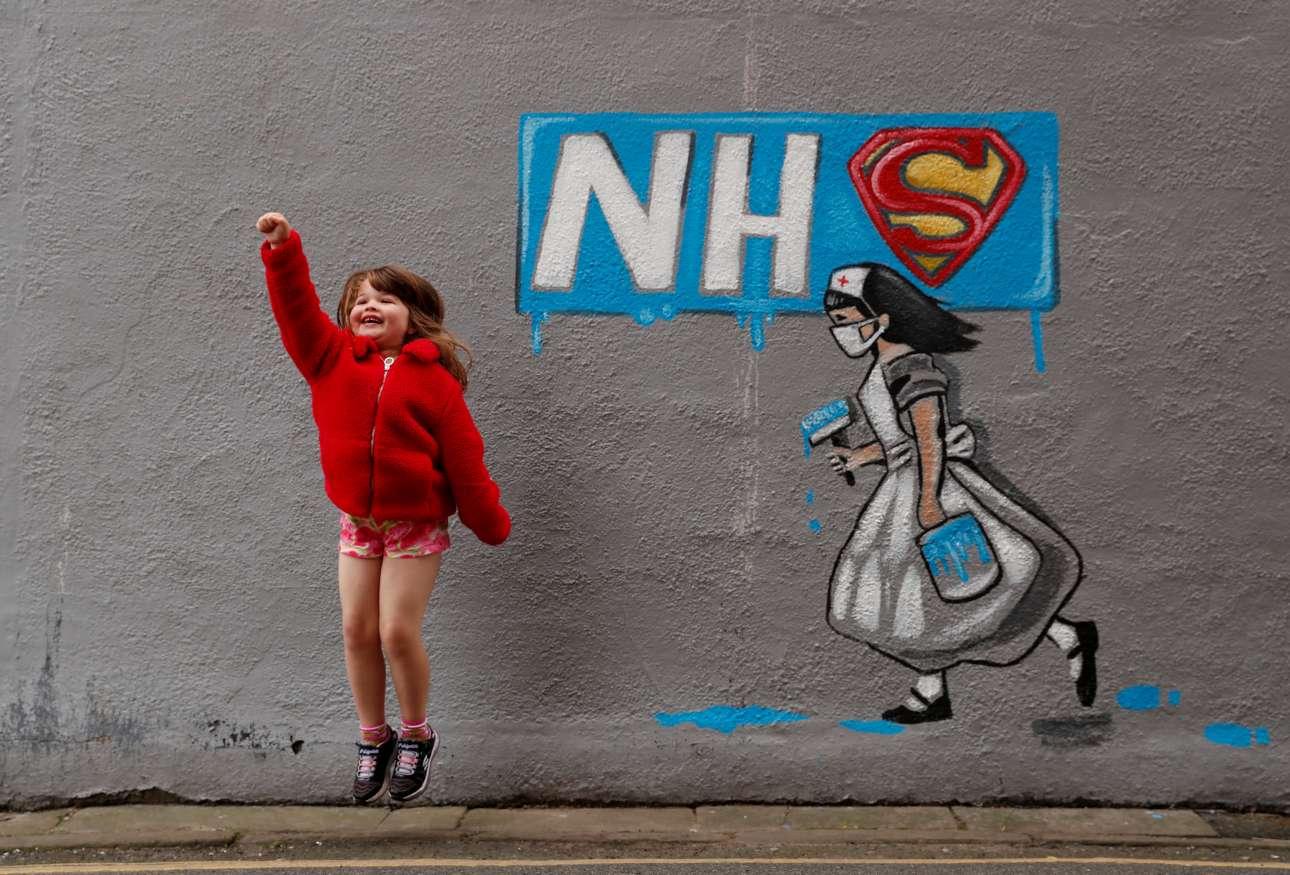 Μια μικρούλα ποζάει μπροστά στο γκράφιτι της καλλιτέχνιδος Ρέιτσελ Λιστ προς τιμήν των γιατρών και των νοσηλευτών του βρετανικού Συστήματος Υγείας (NHS)