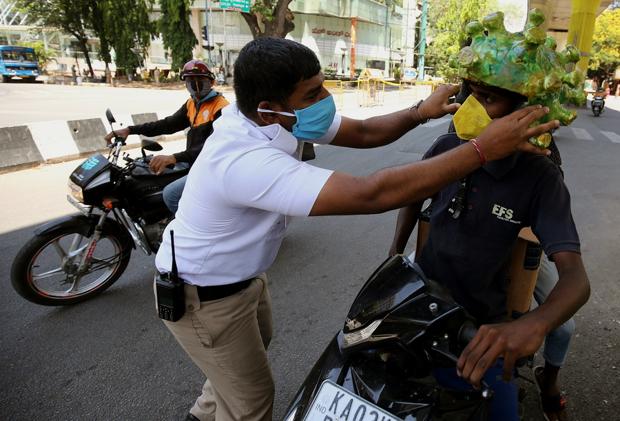 Μπανγκαλόρ, Ινδία. Ο αστυφύλακας (αριστερά) φοράει το αποτρόπαιο κράνος του κορονοϊού σε έναν δύστυχο μοτοσικλετιστή που πρέπει να οργώσει τα σοκάκια, ώστε να τον δει ο κόσμος και να τρέξει αλαφιασμένος να κρυφτεί στο σπίτι