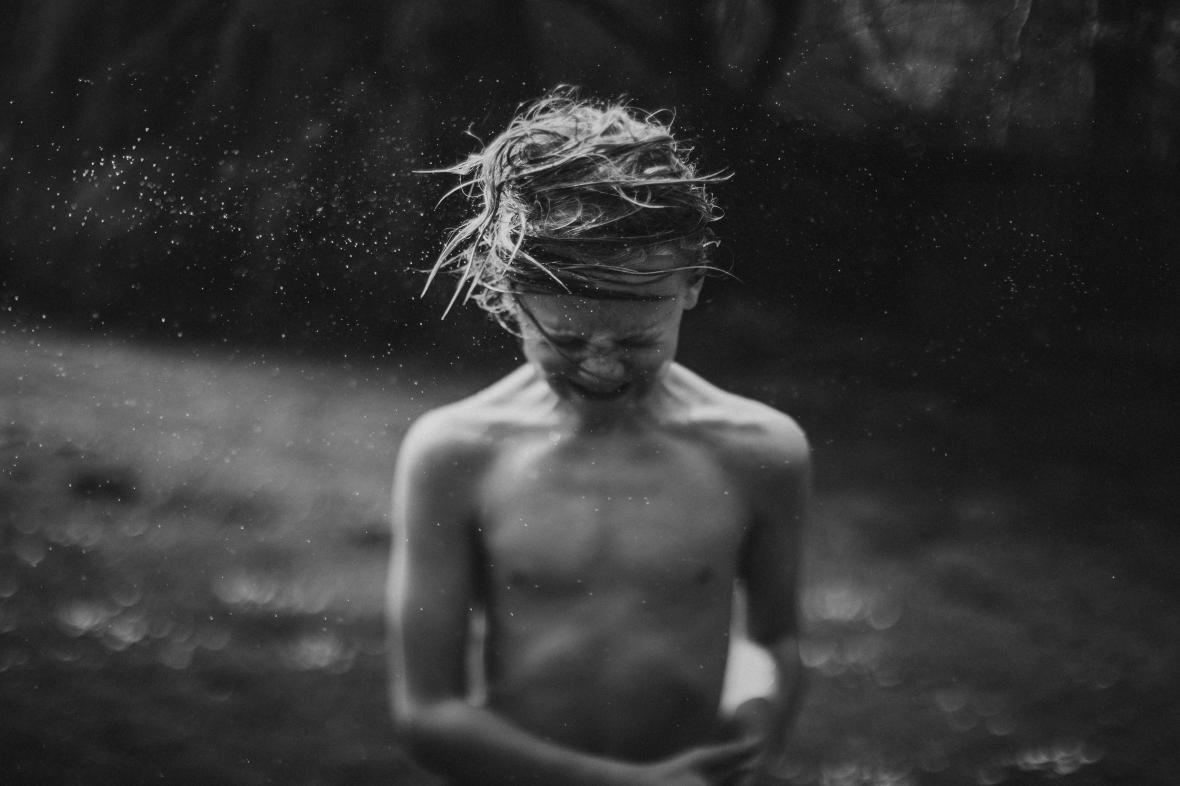 Ένα αγόρι τινάζει το κεφάλι του για να φύγει το νερό από τα αυτιά του μετά από μια βουτιά σε κρύο ποτάμι