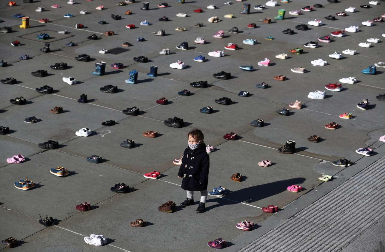 Πλατεία Τραφάλγκαρ, Λονδίνο. Ενα παιδάκι με μάσκα στέκεται ανάμεσα σε 1.500 ζευγάρια παπουτσιών χωρίς παιδικά πέλματα μέσα τους. Πρόκειται για χάπενινγκ της ομάδας Extinction Rebellion, που θέλει οικονομική ανάκαμψη μεν, οικολογική δε
