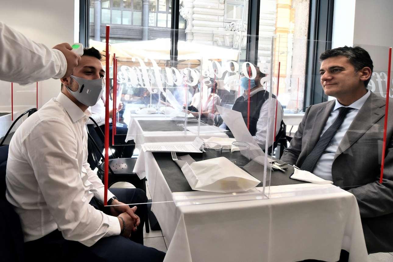 Διαχωριστικά πλέξιγκλας και μέτρηση θερμοκρασίας περιμένουν τους πελάτες σε εστιατόριο στο Μιλάνο
