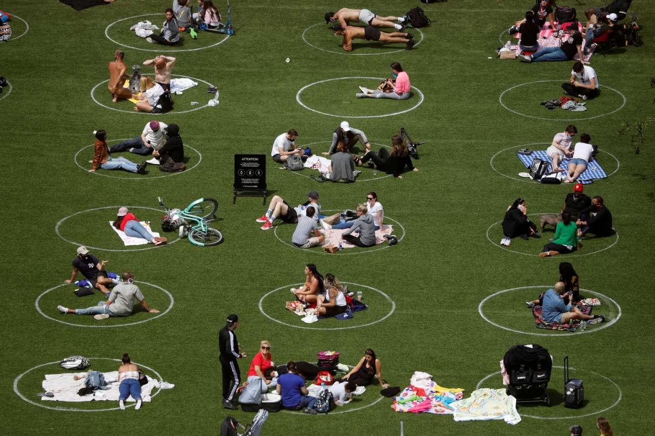 Ανθρωποι χαλαρώνουν και διασκεδάζουν στο πάρκο Ντόμινο στο Μπρούκλιν, μέσα σε βαμμένους στο γρασίδι κύκλους