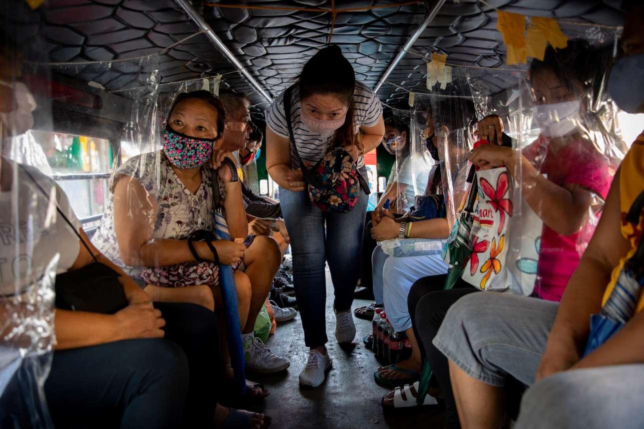 Αυτοσχέδιες μάσκες κάθε είδους φορούν οι επιβάτες αυτού του χαμηλοτάβανου φιλιππινέζικου λεωφορείου