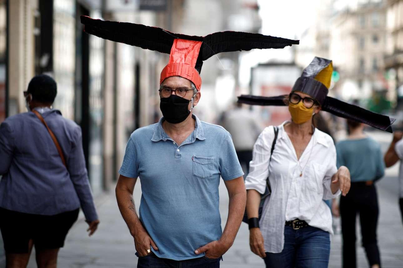 Αυτά που έβαλαν στα κεφάλια τους οι εικονιζόμενοι Παριζιάνοι θεωρούνται καπέλα. Με το πλάτος τους, λέει, κρατούν τις δέουσες αποστάσεις ώστε να μην κολλήσουν κορονοϊό από τους άλλους διαβάτες, που είναι και ξεσκούφωτοι