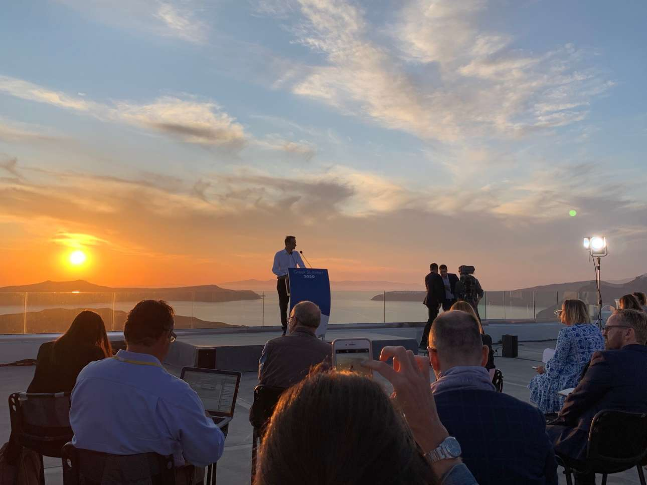 Ο Κυριάκος Μητσοτάκης μιλά σε εκπροσώπους των διεθνών ΜΜΕ με φόντο το υπέροχο δειλινό της Σαντορίνης