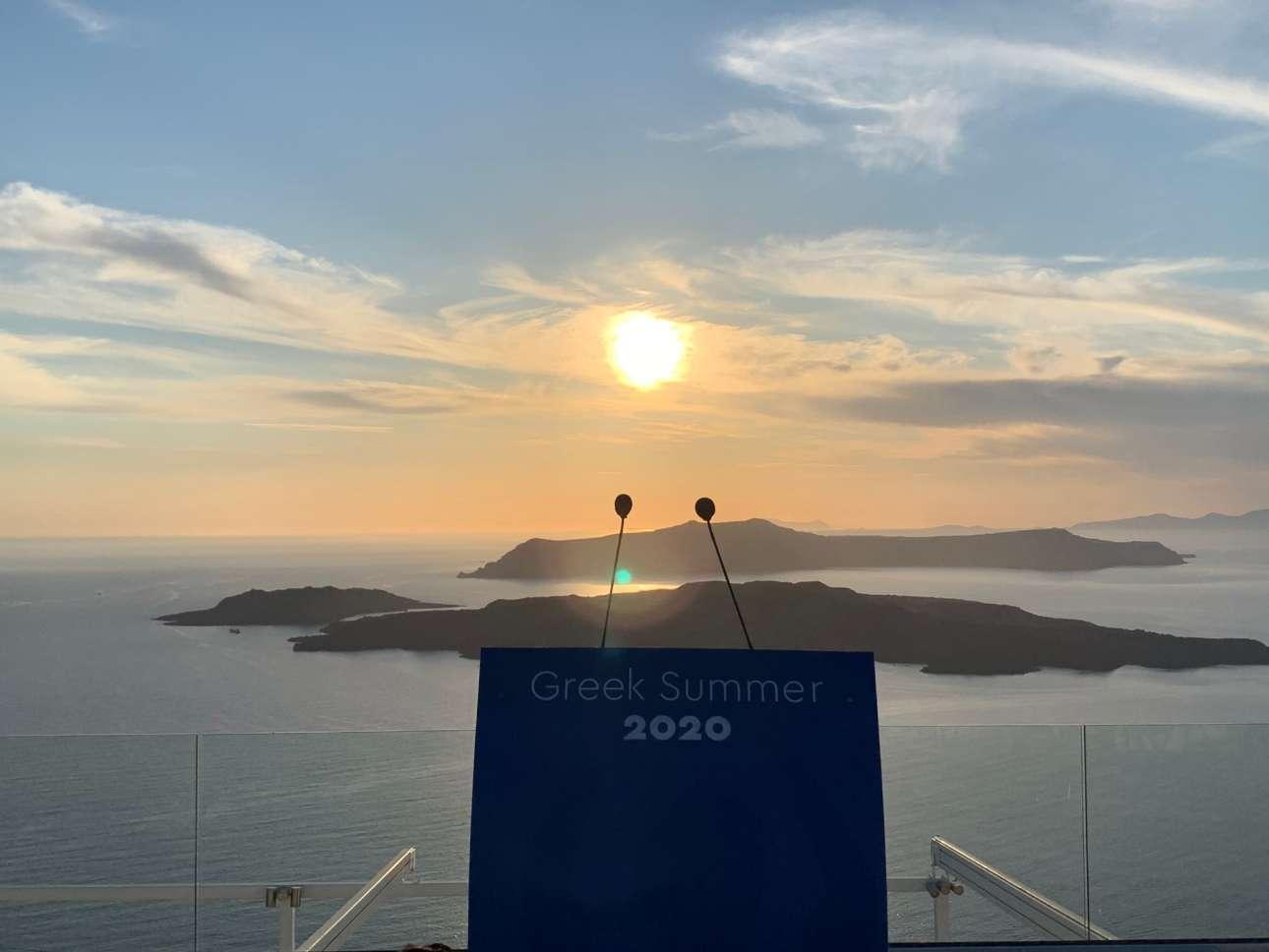 To βήμα έτοιμο με φόντο το εμβληματικό ηλιοβασίλεμα της Σαντορίνης. Το σύνθημα ευκρινές: «Greek Summer 2020»