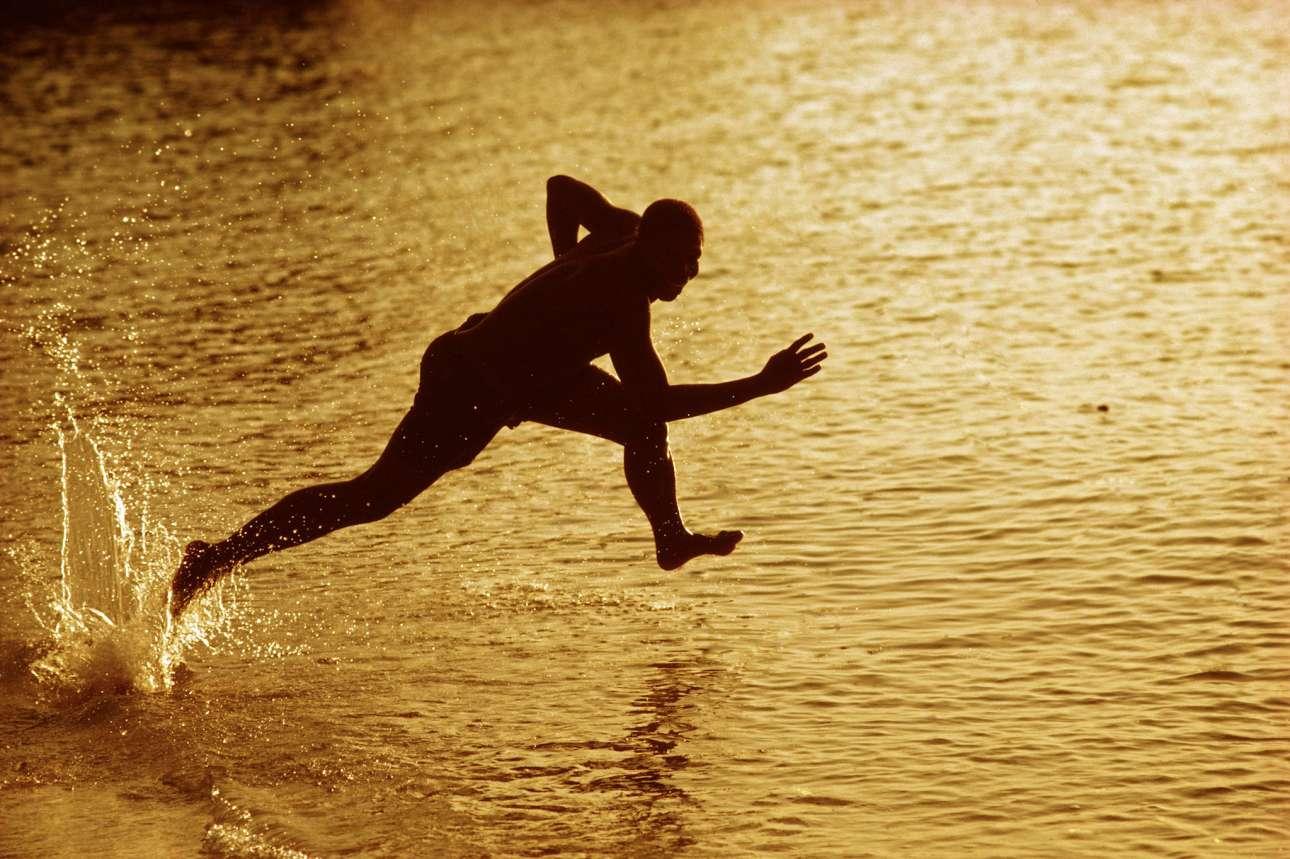 Ενας λουόμενος τρέχει στη θάλασσα καθώς ο ήλιος δύει στη Ζανζιβάρη, 1983