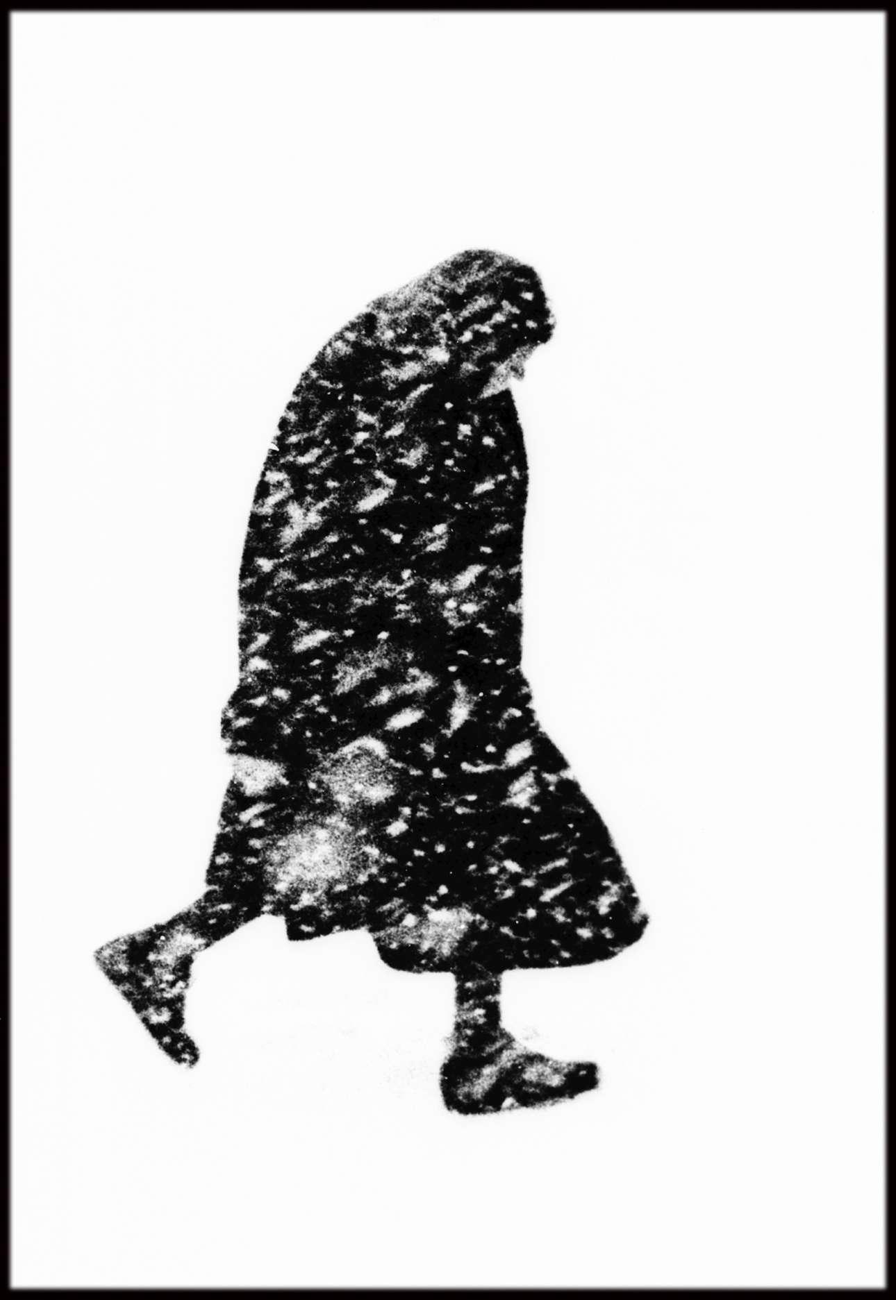 Μία εικόνα που μοιάζει σαν αφαιρετική ζωγραφιά: ηλικιωμένη κυρία περπατάει μέσα σε χιονοθύελλα, στο Αμβούργο το 1954