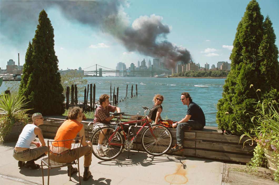 Από τις πιο εμβληματικές εικόνες του Χέπκερ: μία παρέα κάνει διάλειμμα για μεσημεριανό αμέριμνη στο Μπρούκλιν, ενώ στο φόντο μαύρος καπνός βγαίνει από τους φλεγόμενους Δίδυμους Πύργους