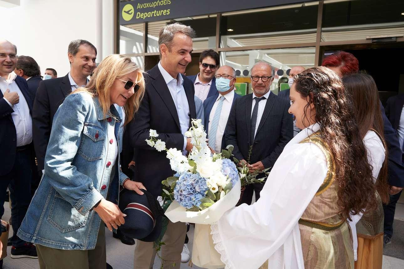 Μερικά άνθη για το πρωθυπουργικό ζεύγος κατά την άφιξη στο νησί. Πίσω διακρίνονται ο υπουργός Τουρισμού Χάρης Θεοχάρης και ο υπουργός Περιβάλλοντος και Ενέργειας Κωστής Χατζηδάκης