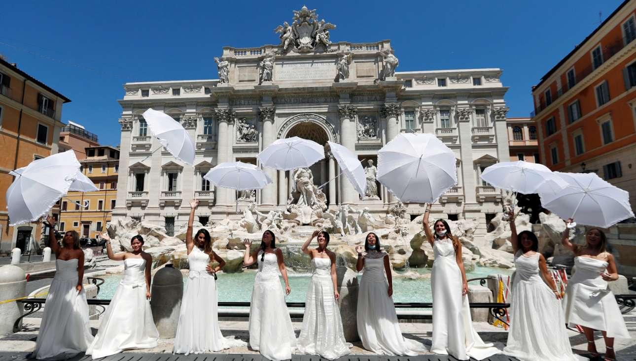 Εκτυφλωτικό λευκό από ομπρελίνα και νυφικά στη ρωμαϊκή Φοντάνα ντι Τρέβι. Μα, τι κάνουν τα κορίτσια; Διαμαρτύρονται, λέει, επειδή οι γάμοι τους αναβλήθηκαν λόγω πανδημίας. Καλά ντε, δεν πήγατε και στα πουρνάρια