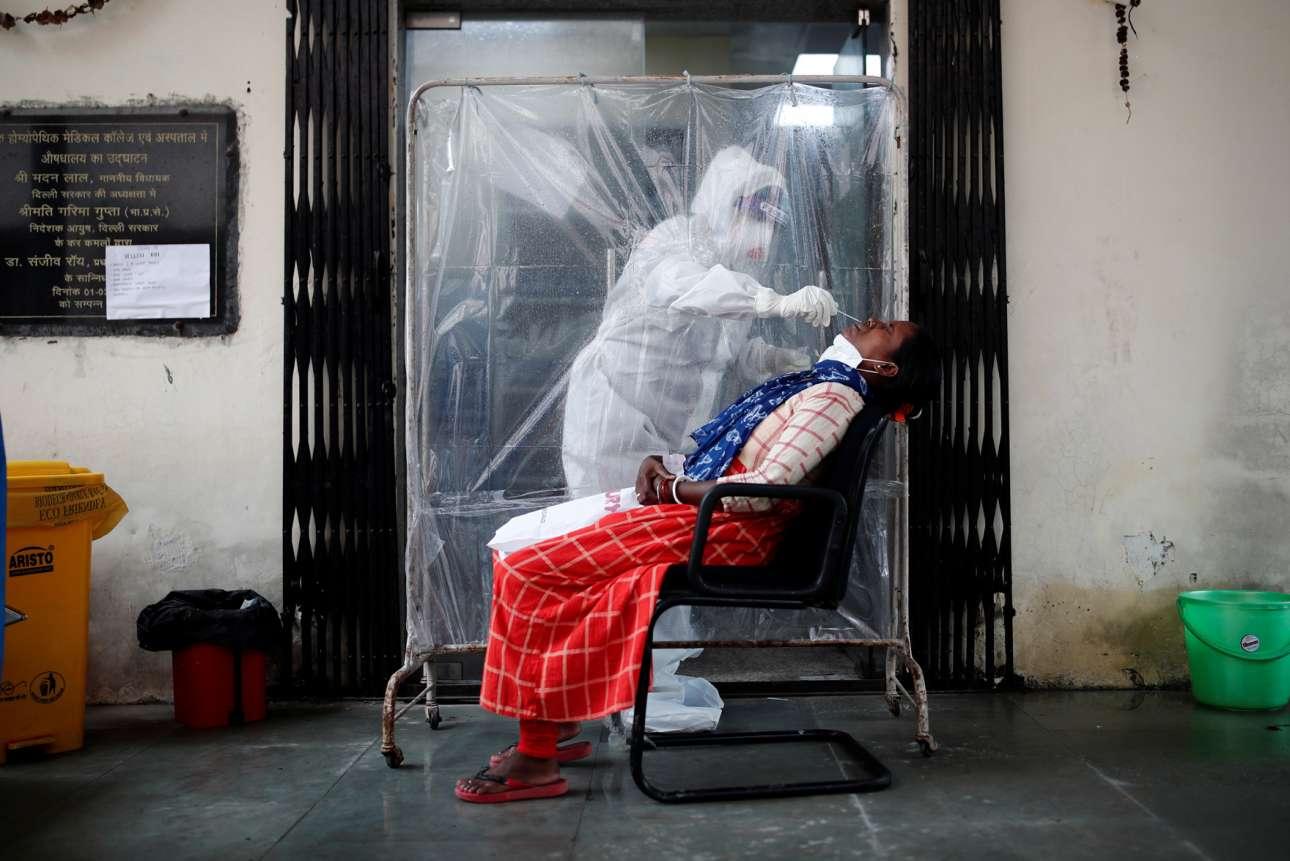 Δείγμα κορονοϊκής δειγματοληψίας από το Νέο Δελχί: ο υγειονομικός υπάλληλος παίρνει το επίχρισμα με εξαιρετική προφύλαξη, αφού μόνο ο δεξιός βραχίονάς του εξέχει από το παραβάν που τον απομονώνει από τον δυνητικό ασθενή