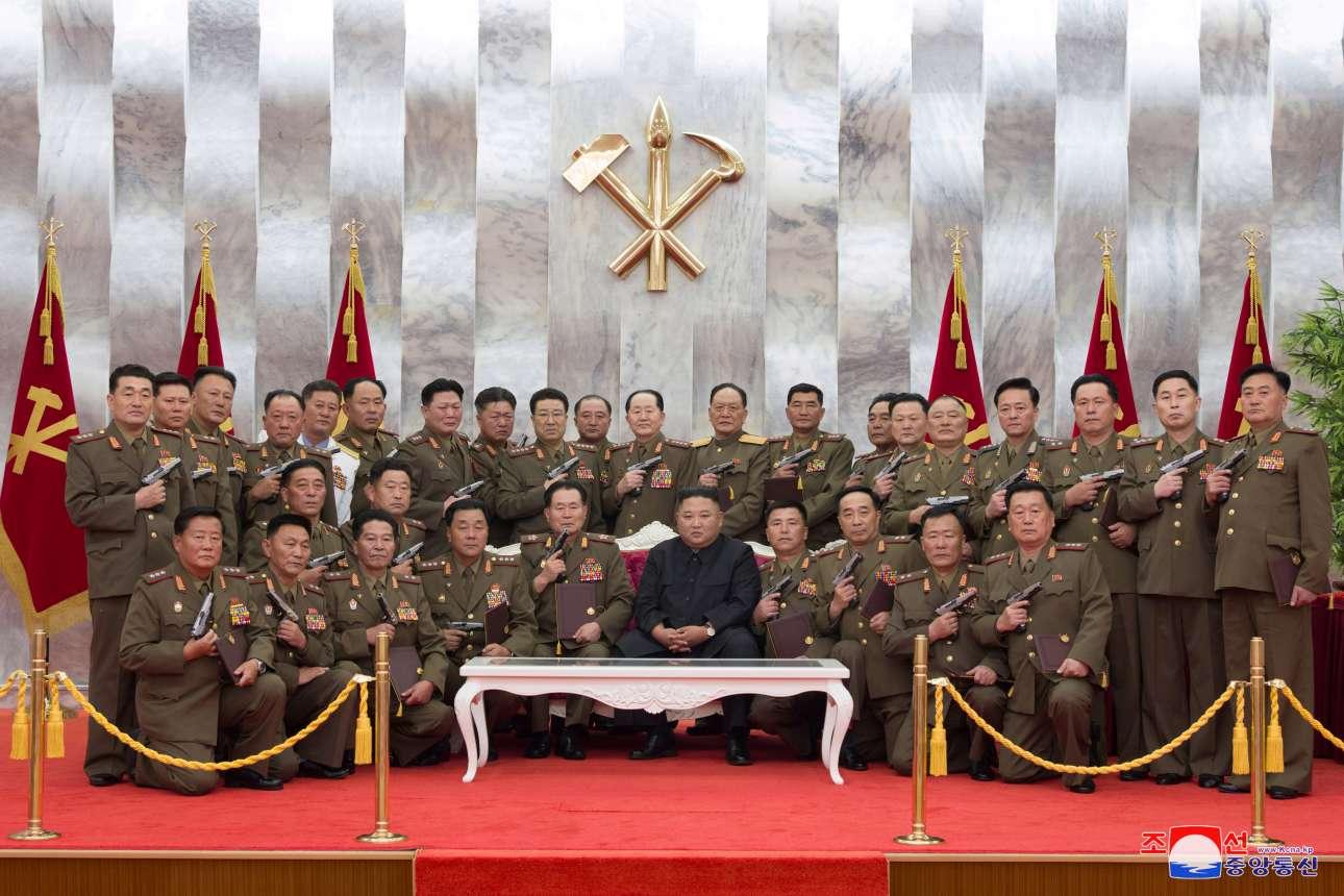 Ο Κιμ και οι άνθρωποί του –φυσικά ανώτατοι αξιωματικοί των Ενόπλων Δυνάμεων της Βορείου Κορέας– σε μια μιλιταριστική πόζα: όλοι, πλην του ηγέτη, επιδεικνύουν τα αναμνηστικά πιστόλια «Paektusan» που τιμούν την Ανακωχή της 27ης Ιουλίου 1953 και το (επιτυχημένο για την Πιονγιάνγκ) τέλος του Πολέμου της Κορέας