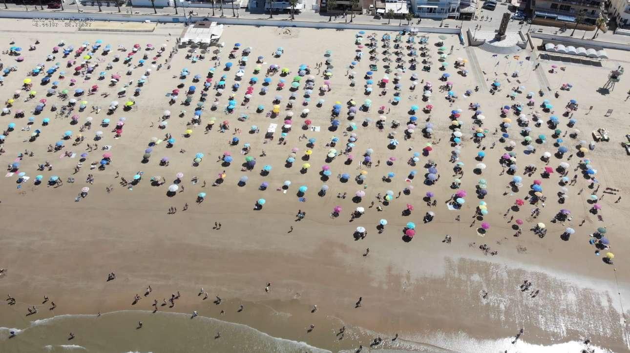 Οι λουόμενοι στην ακτή αυτή της Τσιπιόνα στη δυτική Ισπανία, έχουν τοποθετήσει τις ομπρέλες τους προσεκτικά, σχεδόν αλφαδιασμένα, σε μια προσπάθεια να τηρήσουν το social distancing