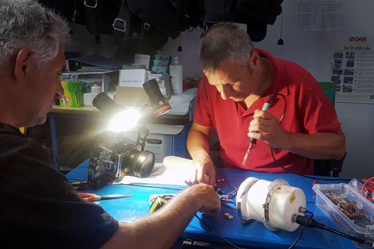 Ο Γιώργος Παπαλάμπρου (με το κόκκινο μπλουζάκι), μέλος της ομάδας συντήρησης του χώρου και επίκουρος καθηγητής στη Σχολή Ναυπηγών Μηχανολόγων Μηχανικών του ΕΜΠ, προετοιμάζει μια υποβρύχια κάμερα