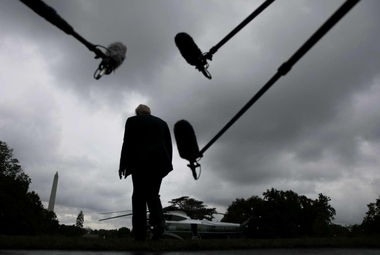 Παρασκευή, 31 Ιουλίου, Ουάσινγκτον. Ο Ντόναλντ Τραμπ μοιάζει να καταδιώκεται από τα μικρόφωνα των ΜΜΕ καθώς ετοιμάζεται να επιβιβαστεί στο Marine One, το προεδρικό ελικόπτερο, για ένα ακόμα Σαββατοκύριακο στη Φλόριντα