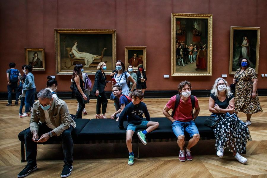 Επισκέπτες του Λούβρου φορούν μάσκες και χαζεύουν με το πάσο τους τα εκλεκτά εκθέματα. Σχεδόν τέσσερις μήνες ήταν κλειστό το παριζιάνικο μουσείο. Προτού κλείσει, σε αυτήν εδώ τη σάλα επικρατούσε, φυσικά, το αδιαχώρητο