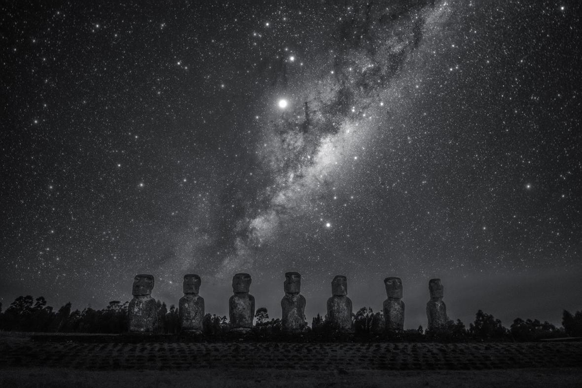 Ο Γαλαξίας αναδύεται πίσω από τα αγάλματα μοάι στο Νησί του Πάσχα, στον Ειρηνικό. H παραπάνω φωτογραφία τονίζει την κεντρική διόγκωση του Γαλαξία, τον αστερισμό του Σκορπιού και τους πλανήτες Δία και Κρόνο