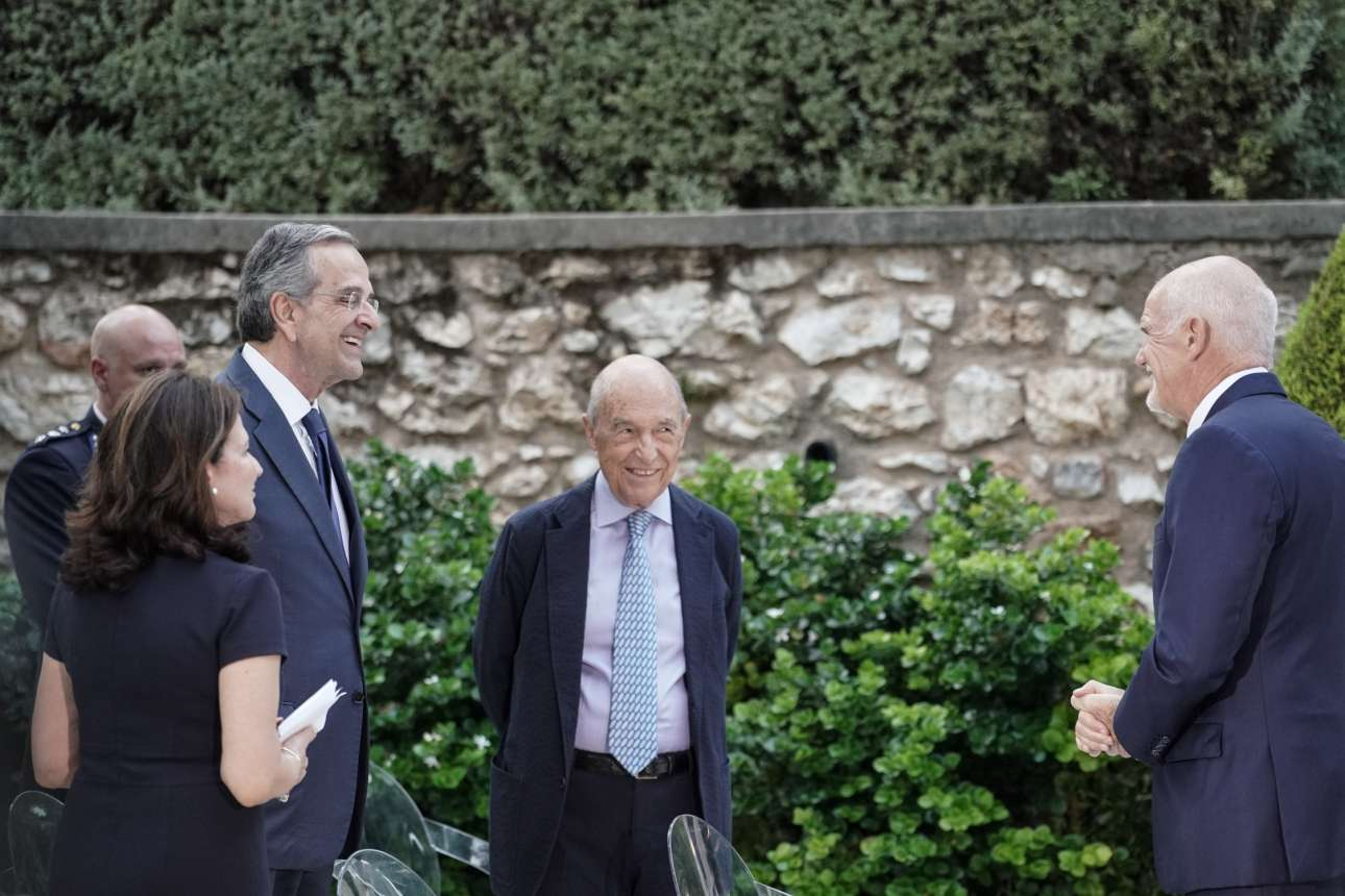 Με κάποιο ασυνήθιστο για την ιδιοσυγκρασία του σκέρτσο, ο πρώην Πρωθυπουργός Κώστας Σημίτης καλωσορίζει στην ομήγυρη τον Γιώργο Παπανδρέου υπό το βλέμμα ενός τρίτου Πρωθυπουργού, του Αντώνη Σαμαρά