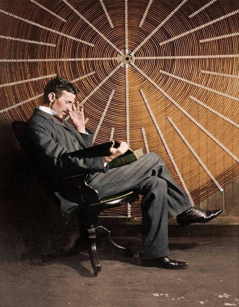 Ο Νίκολα Τέσλα διαβάζει μπροστά από την σπείρα του μετασχηματιστή του υψηλής συχνότητας