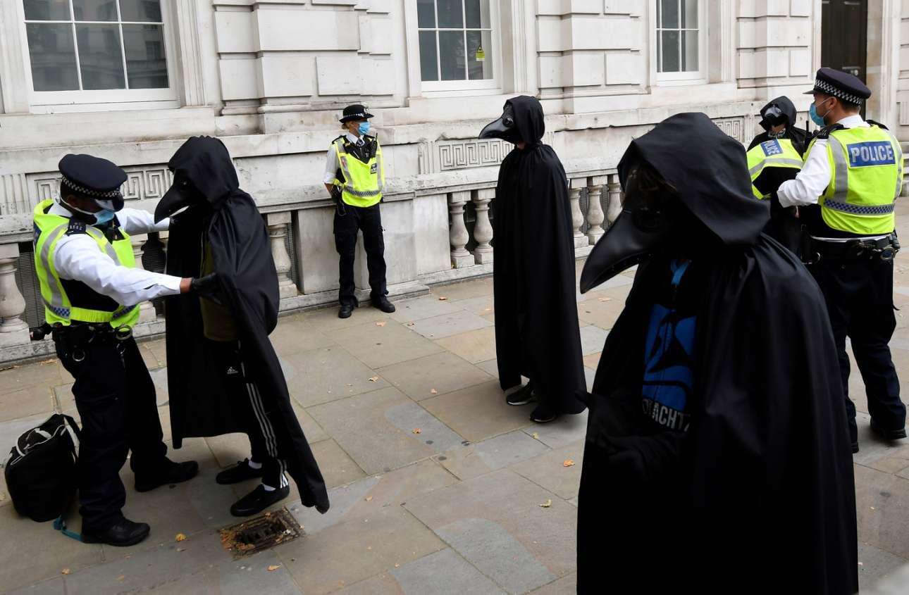 Δεν είναι μεταλλαγμένοι κόρακες, ούτε αμερικανοί σατανιστές που δραπέτευσαν από το «Μάτια ερμητικά κλειστά» επειδή δαιμονίστηκαν με το «ρώσικο βαλς» (του Σοστακόβιτς). Είναι οικολόγοι που βγήκαν στο Λονδίνο να διαμαρτυρηθούν αλλά έπεσαν σε αστυνομική παγάνα που είχε για ξόβεργες τα κλομπ