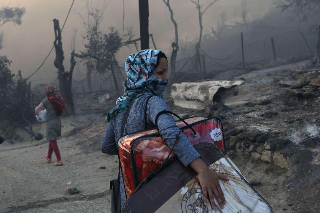 Για μια ακόμα φορά πρόσφυγας. Με τα λιγοστά υπάρχοντα στην αγκαλιά, η γυναίκα αυτή αποχωρεί από τον χώρο του ΚΥΤ