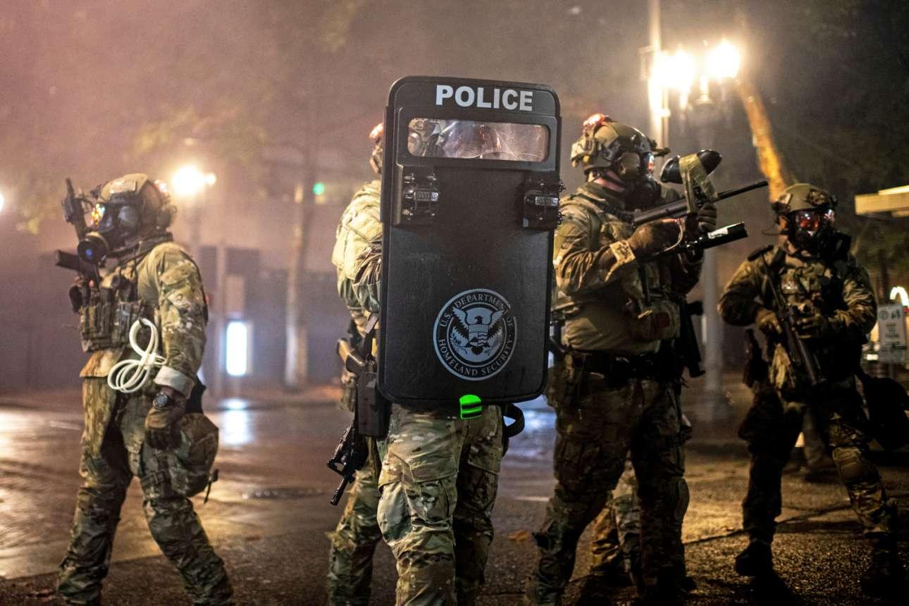 Πόρτλαντ. Πάνοπλοι άνδρες των δυνάμεων καταστολής φρουρούν δημόσια κτίρια της αμερικανικής πόλης κατά τη διάρκεια επεισοδιακών διαδηλώσεων μαύρων. Προηγήθηκε δικαστική απόφαση εν μέρει αθωωτική για αστυνομικούς που σκότωσαν μαύρη