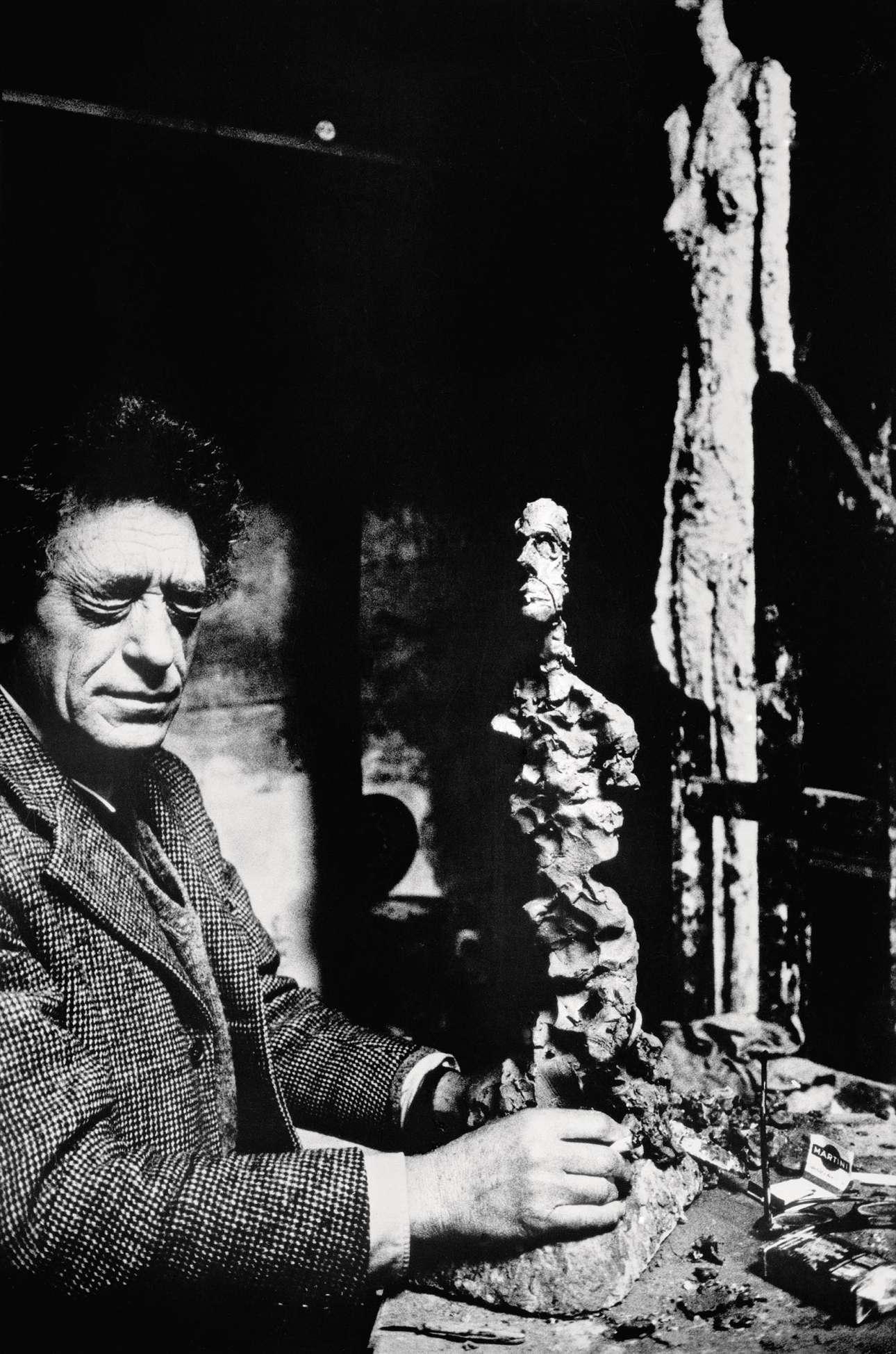 Ο ελβετός γλύπτης Αλμπέρτο Τζιακομέτι με κλειστά μάτια αγγίζει τις μακρόστενες, απόκοσμες φιγούρες του στο ατελιέ του, στη περιοχή Μονπαρνάς του Παρισιού, το 1960