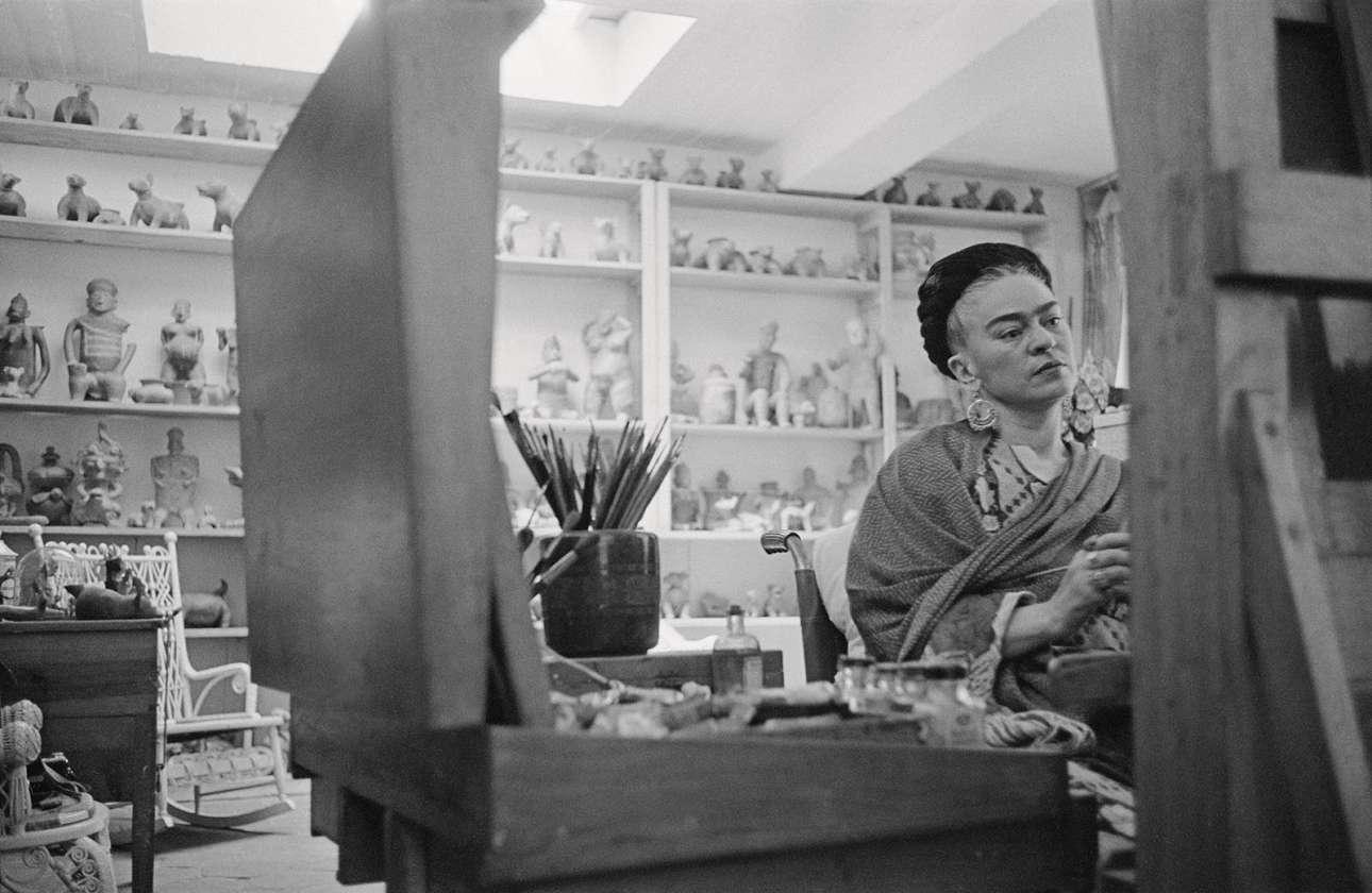 Η Φρίντα Κάλο στην Πόλη του Μεξικού, το 1954. Τους τελευταίους μήνες της ζωής της, η Κάλο ζωγράφιζε από την αναπηρική της καρέκλα μέσα στο γεμάτο από γλυπτά στούντιο της