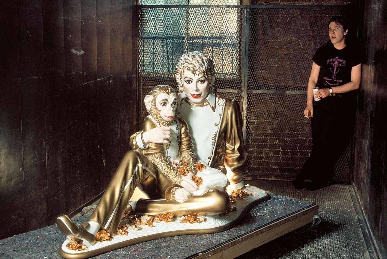 Μανχάταν, Νέα Υόρκη, 1989: ο Τζεφ Κουνς, ο πιο ακριβοπληρωμένος καλλιτέχνης γνωστός για τα κιτς έργα του εμπνευσμένα από την ποπ κουλτούρα, ποζάρει δίπλα στο πορσελάνινο γλυπτό του Μάικλ Τζάκσον αγκαλιά με τον πίθηκο του Μπάμπλς