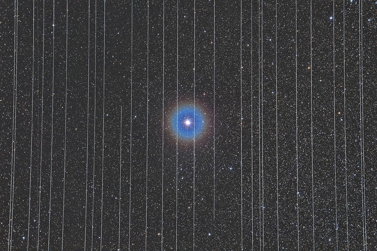 Μια διαστημική φυλακή. Μοιάζει με ένα άστρο που το έχουν φυλακίσει. Στην πραγματικότητα είναι ο διπλός αστέρας Albireo που εικονίζεται πίσω από τα ίχνη που αφήνουν που αφήνουν στον ουρανό ορισμένοι από τους εμπορικούς δορυφόρους που κινούνται σε τροχιά γύρω από τη Γη. Η φωτογραφία του Ούγγρου Rafael Schmall κέρδισε το πρώτο βραβείο της κατηγορίας «Άνθρωποι και Διάστημα», αποτυπώνοντας τόσο την πρόοδο του ανθρώπινου πολιτισμού όσο και την παρέμβασή του, όχι πια στο φυσικό τοπίο της Γης, αλλά στο διαστημικό πλέον τοπίο