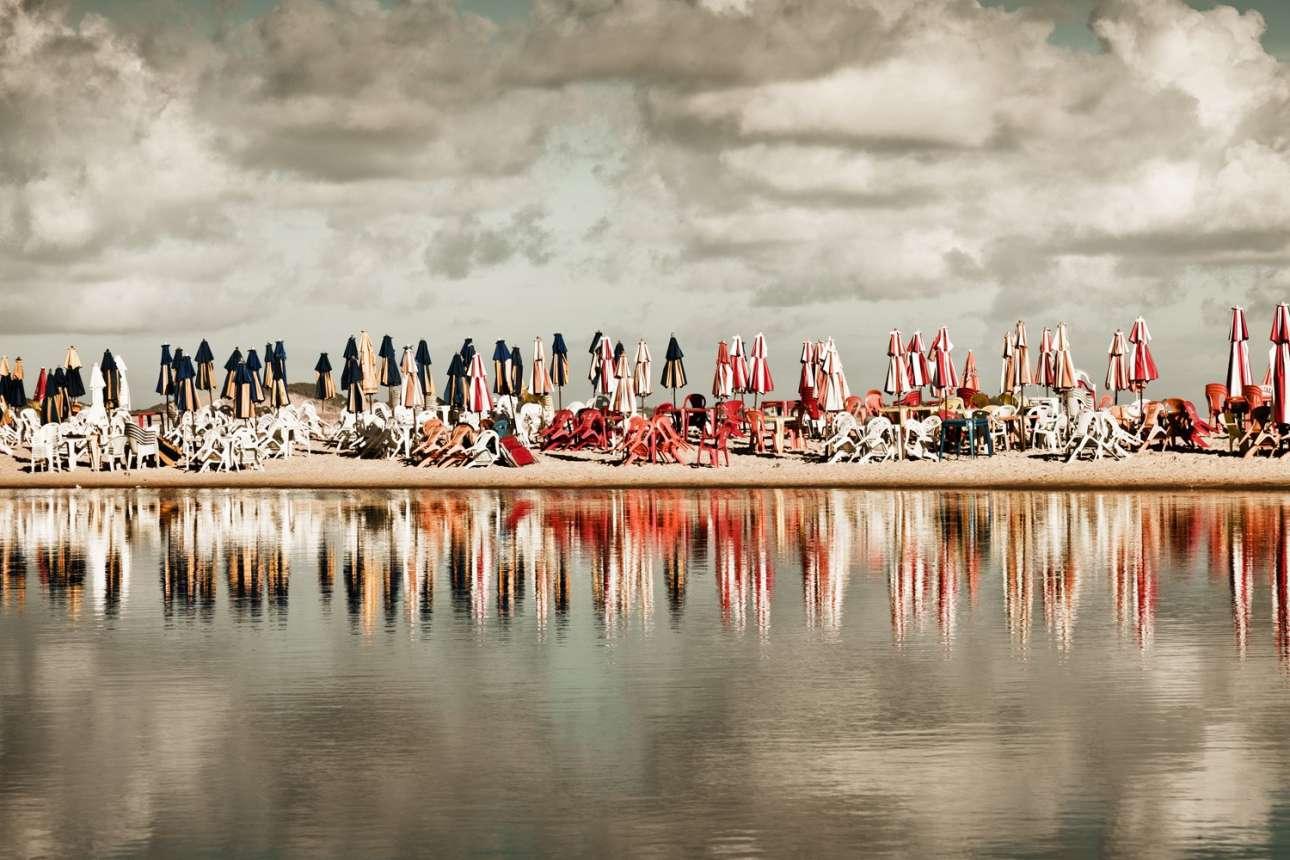 Κατηγορία «Ωκεανοί, Θάλασσες, Ποτάμια, Λίμνες». Πλαστικές καρέκλες και ομπρέλες στην άμμο είναι όλα όσα απέμειναν σε παραλία της Βραζιλίας, ύστερα από μια μεγάλη νύχτα εορτασμών για την Πρωτοχρονιά