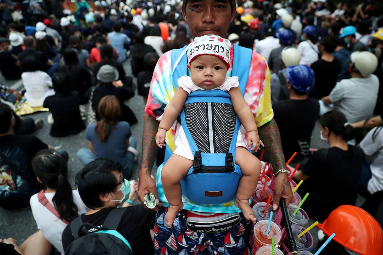 Μπανγκόκ. Διαδηλώσεις στην Ταϊλάνδη και διαδηλώσεις δεν γίνονται χωρίς δροσιστικά και καφέδες. Εδώ βλέπουμε τον πωλητή αναψυκτικών και το μωρό του