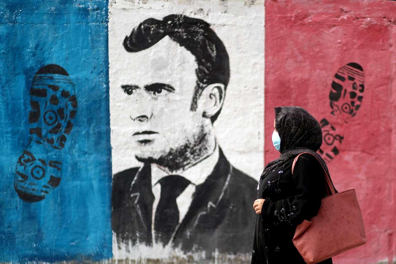Γάζα. Ο παλαιστίνιος ζωγράφος στόλισε το πορτρέτο του Μακρόν και τη γαλλική σημαία με αποτυπώματα υποδημάτων, θέλοντας να επιστρέψει την προσβολή που ως μουσουλμάνος ένιωσε από την υπόθεση των γελοιογραφιών